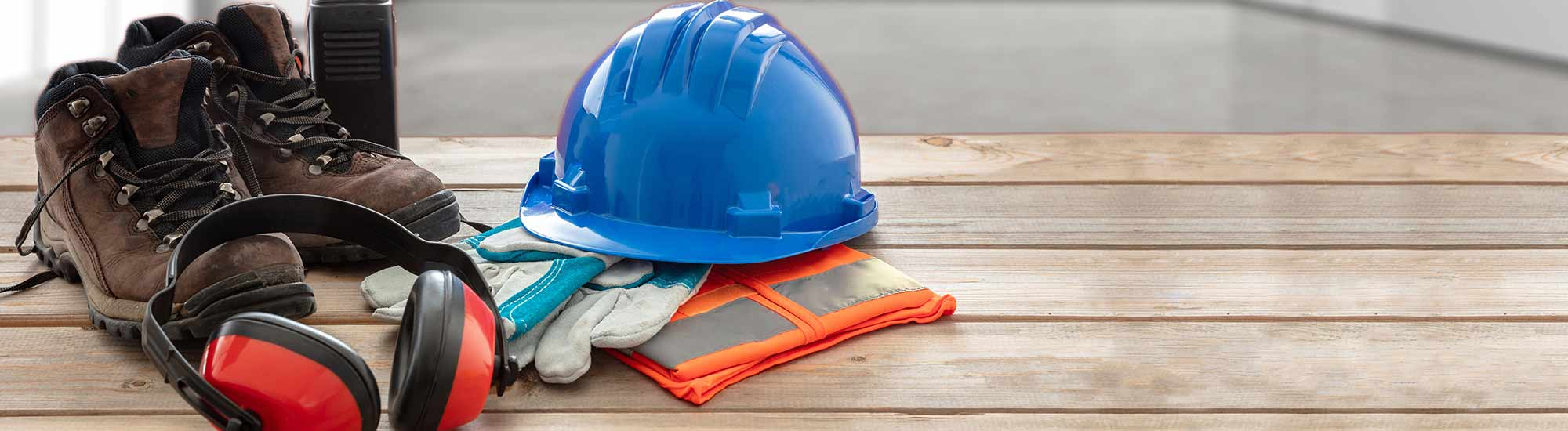 Work safety protection equipment. Industrial protective gear on wooden table, blur office or home interior background. Hardhat, boots, earmuffs, gloves, goggles