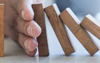 Hand stoppt fallende Dominosteine